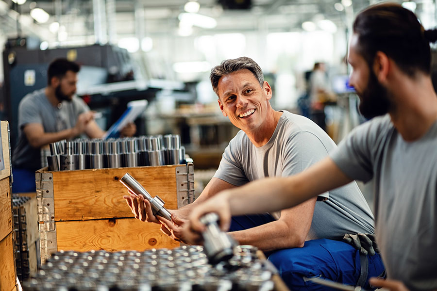 Specialized Business Insurance - Smiling Employees Working In Manufacturing Facility